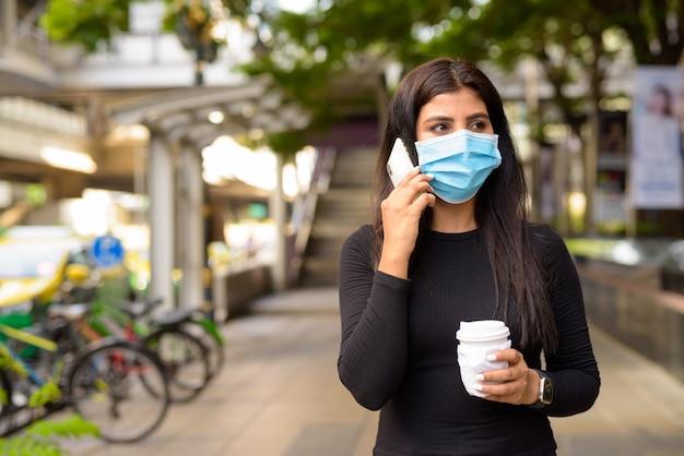 Junge inderin mit maske, die am telefon spricht und kaffee unterwegs als neue normalität während covid-19 trinkt
