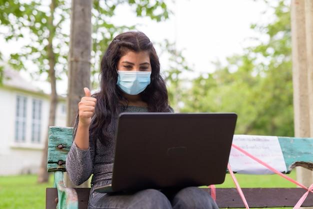 Junge inderin mit maskenvideoanruf und daumenaufgabe beim sitzen mit abstand auf parkbank