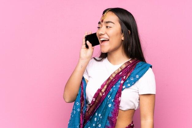 Junge inderin mit sari, die ein gespräch mit dem handy hält