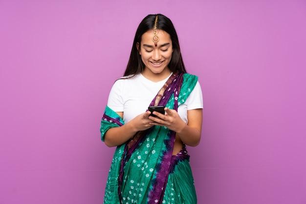 Junge inderin mit sari über isoliertes senden einer nachricht mit dem handy