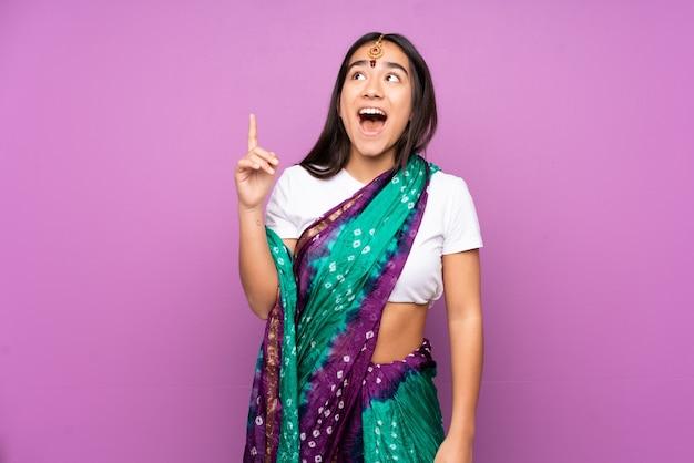 Junge inderin mit sari zeigt und überrascht