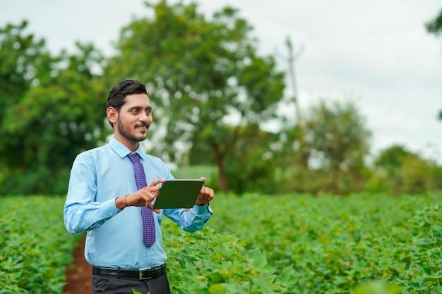 Junge indische agronom oder offizier mit tablet im landwirtschaftsfeld.