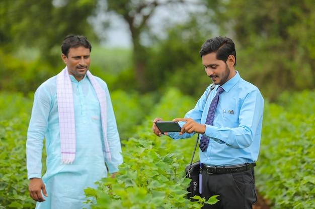 Junge indische agronomen oder banker, die dem landwirt im smartphone im landwirtschaftsbereich einige informationen zeigen.