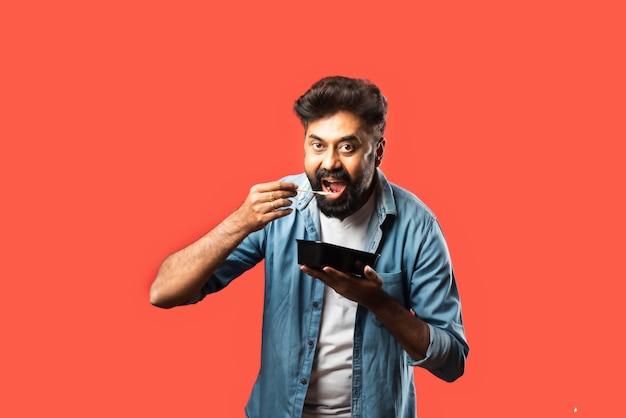 Junge indische asiatische mann essen zum mitnehmen in der box mit löffel oder stäbchen, stehend auf rot