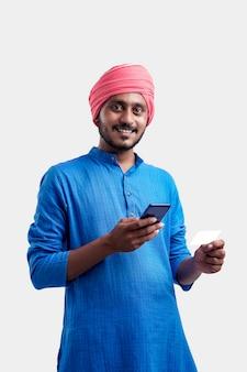 Junge indische bauer mit smartphone und bankkarte auf weißem hintergrund.