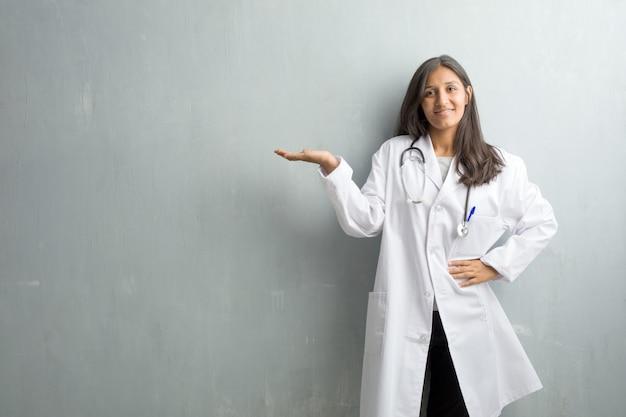 Junge indische doktorfrau gegen eine wand, die etwas mit den händen, ein produkt zeigend hält