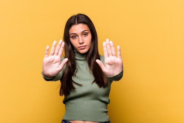 Junge indische frau auf gelbem stehen mit ausgestreckter hand, die stoppschild zeigt, das sie verhindert.