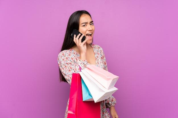 Junge indische frau auf lila wand, die einkaufstaschen hält und einen freund mit ihrem handy anruft