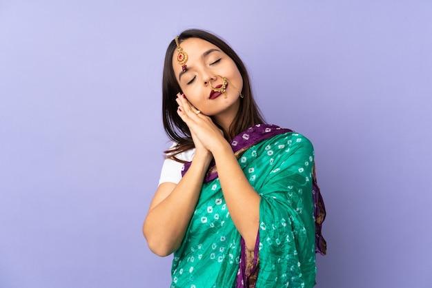 Junge indische frau auf lila wand, die schlafgeste macht