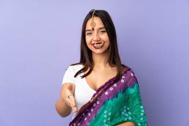 Junge indische frau auf lila wand händeschütteln für den abschluss eines deals