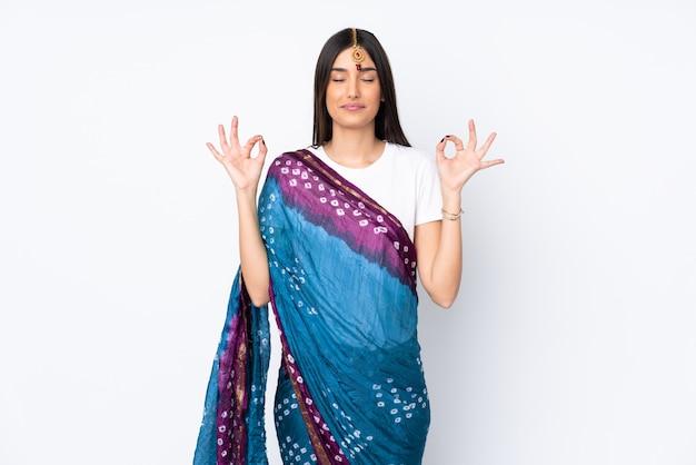 Junge indische frau auf weißer wand in zen-pose