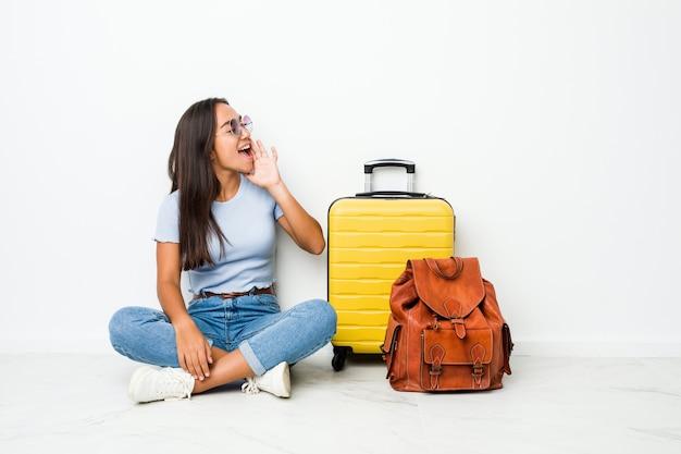 Junge indische frau der gemischten rasse, die bereit ist, zu reisen, schreiend und handfläche nahe geöffnetem mund haltend.