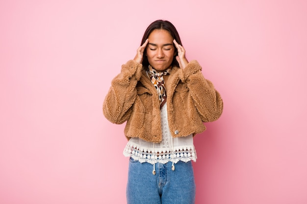 Junge indische frau der gemischten rasse, die ein kurzes schaffell trägt, das schläfen coattouching und kopfschmerzen hat.