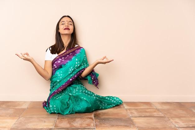 Junge indische frau, die auf dem boden in zen-pose sitzt