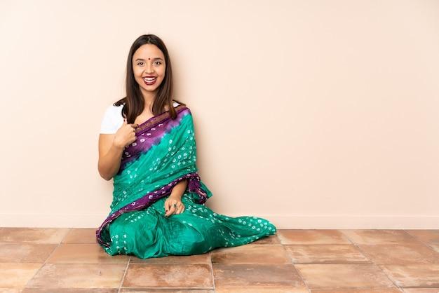 Junge indische frau, die auf dem boden mit überraschendem gesichtsausdruck sitzt