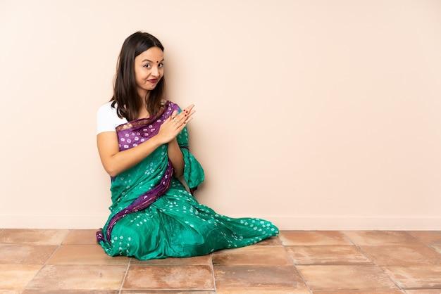 Junge indische frau, die auf dem boden sitzt, der etwas entwirft
