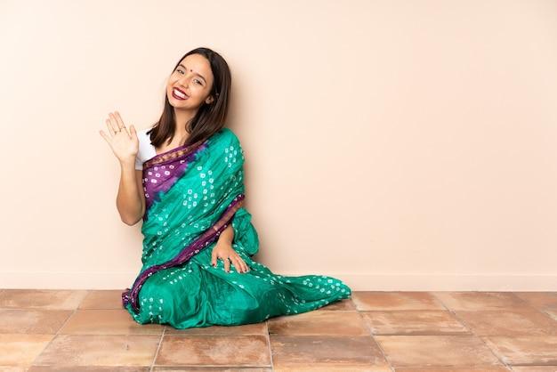 Junge indische frau, die auf dem boden sitzt, der mit hand mit glücklichem ausdruck salutiert