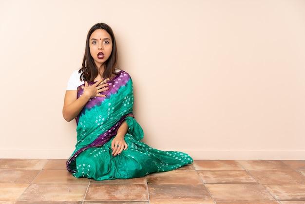 Junge indische frau, die auf dem boden sitzt, überrascht und schockiert, während sie richtig schaut