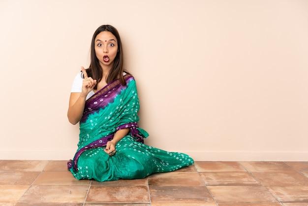 Junge indische frau, die auf dem boden sitzt und beabsichtigt, die lösung zu realisieren, während sie einen finger anhebt Premium Fotos