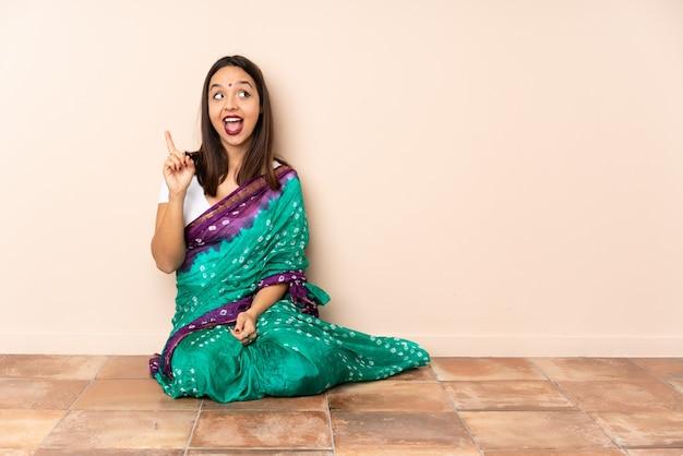 Junge indische frau, die auf dem boden sitzt und beabsichtigt, die lösung zu realisieren, während sie einen finger anhebt