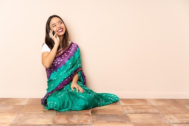 Junge indische frau, die auf dem boden sitzt und ein gespräch mit dem mobiltelefon hält