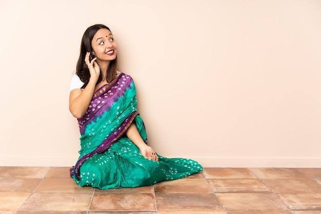 Junge indische frau, die auf dem boden sitzt und ein gespräch mit dem mobiltelefon mit jemandem hält