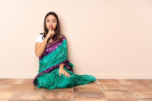 Junge indische frau, die auf dem boden sitzt und ein zeichen der schweigegeste zeigt, das finger in mund setzt