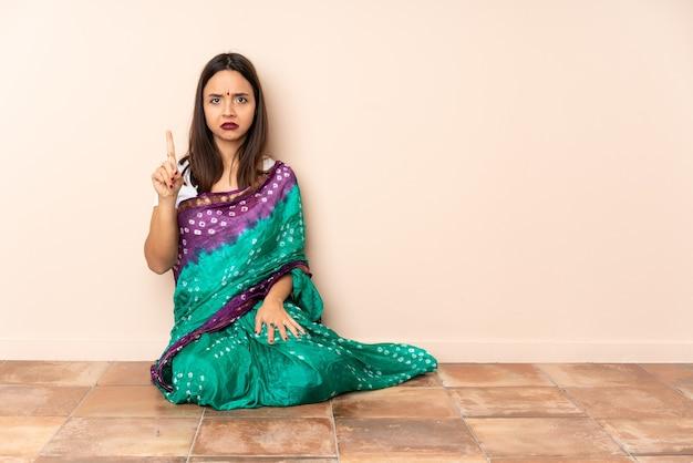Junge indische frau, die auf dem boden sitzt und eins mit ernstem ausdruck zählt