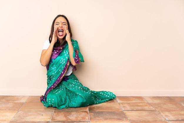 Junge indische frau, die auf dem boden sitzt und etwas schreit und ankündigt