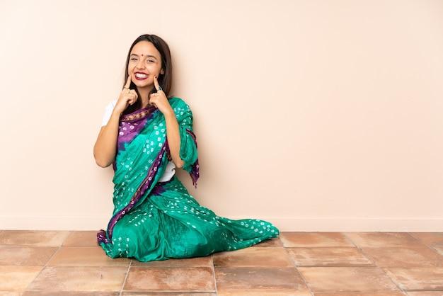 Junge indische frau, die auf dem boden sitzt und mit einem glücklichen und angenehmen ausdruck lächelt