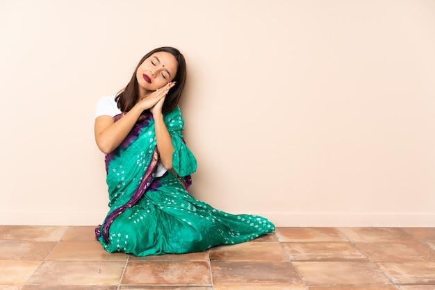 Junge indische frau, die auf dem boden sitzt und schlafgeste in liebenswürdigem ausdruck macht