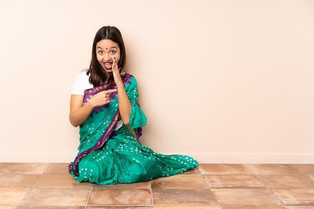 Junge indische frau, die auf dem boden sitzt und zur seite zeigt, um ein produkt zu präsentieren und etwas zu flüstern