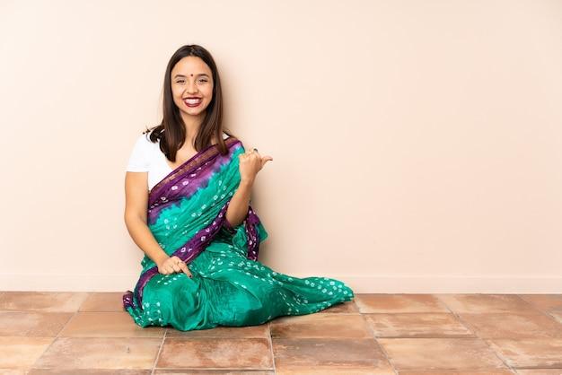 Junge indische frau, die auf dem boden sitzt und zur seite zeigt, um ein produkt zu präsentieren