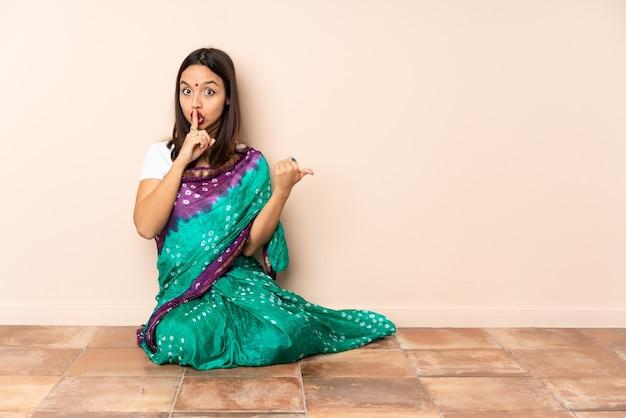 Junge indische frau, die auf dem boden sitzt und zur seite zeigt und schweigegeste tut