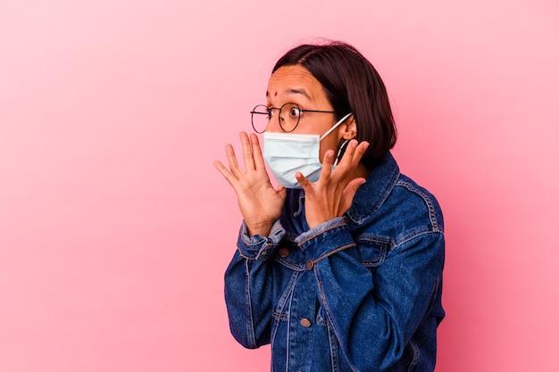 Junge indische frau, die ein auf rosafarbenem hintergrund isoliertes masken-antivirus trägt, schreit laut, hält die augen geöffnet und die hände angespannt.