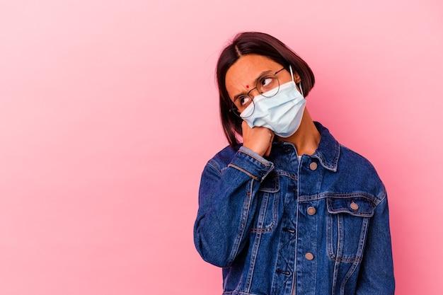 Junge indische frau, die ein masken-antivirus trägt, das auf rosa lokalisiert wird, der sich traurig und nachdenklich fühlt und kopierraum betrachtet.