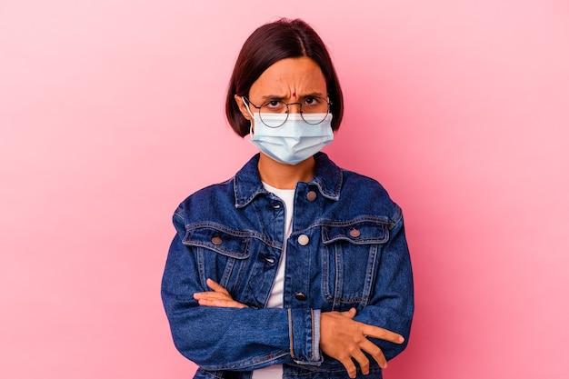Junge indische frau, die ein masken-antivirus trägt, das auf rosa stirnrunzelndem gesicht in missfallen isoliert wird, hält arme verschränkt.