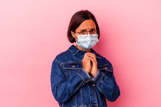 Junge indische frau, die ein masken-antivirus trägt, isoliert auf rosa ängstlich und ängstlich.