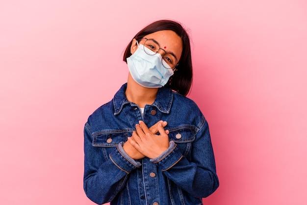 Junge indische frau, die ein maskenantivirus trägt, das auf rosa isoliert wird, hat freundlichen ausdruck, der handfläche zur brust drückt