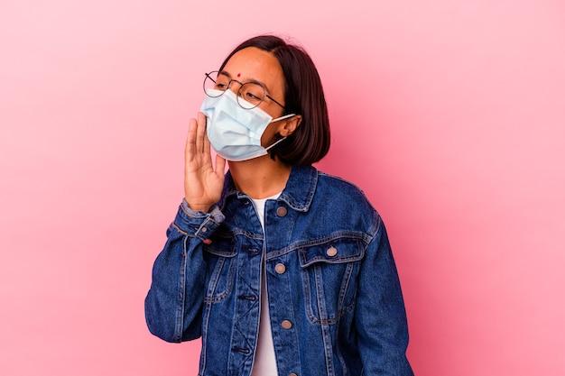 Junge indische frau, die eine maske antivirus lokalisiert auf rosa hintergrund schreit und palme nahe geöffnetem mund hält.