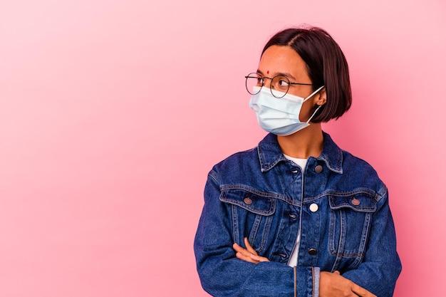 Junge indische frau, die eine maske antivirus lokalisiert auf rosa lächelnd zuversichtlich mit verschränkten armen trägt.