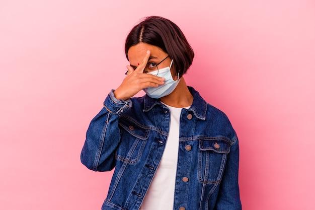 Junge indische frau, die eine maske antivirus trägt, die auf rosa blinzeln an der kamera durch finger, verlegenes bedeckendes gesicht isoliert wird.