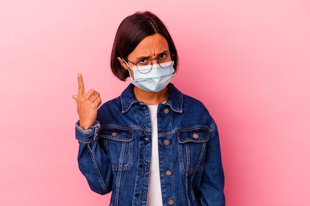 Junge indische frau, die eine maske trägt, die auf rosafarbenem hintergrund isoliert ist und eine enttäuschungsgeste mit dem zeigefinger zeigt.