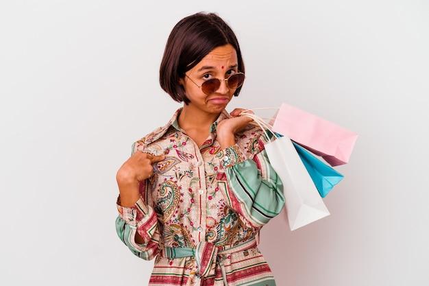 Junge indische frau, die einige kleidungsstücke lokalisiert auf weißer hintergrundperson kauft, die von hand auf einen hemdkopierraum zeigt, stolz und zuversichtlich