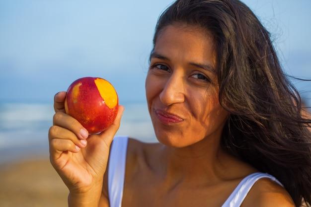 Junge indische frau, die frucht auf dem strand isst