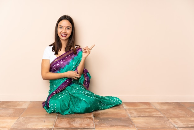Junge indische frau, die glücklich auf dem boden sitzt und nach oben zeigt
