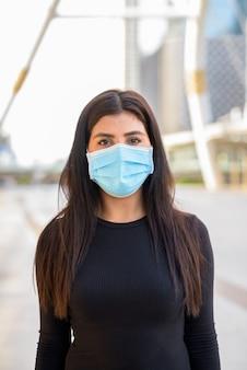 Junge indische frau, die maske zum schutz vor coronavirus-ausbruch an der skywalk-brücke trägt