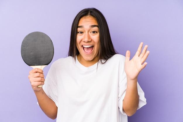 Junge indische frau, die tischtennis spielt isoliert, feiert einen sieg oder erfolg