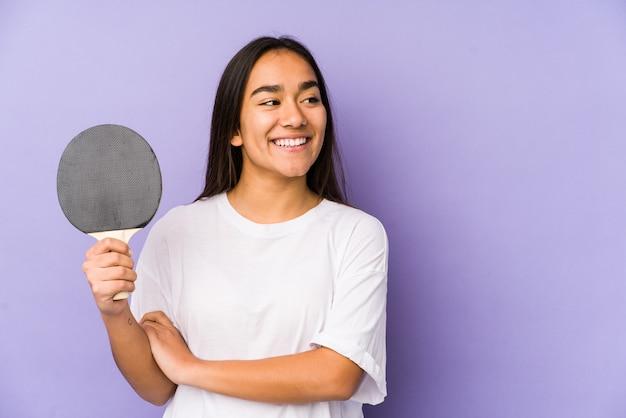 Junge indische frau, die tischtennis spielt, isoliert lächelnd zuversichtlich mit verschränkten armen.