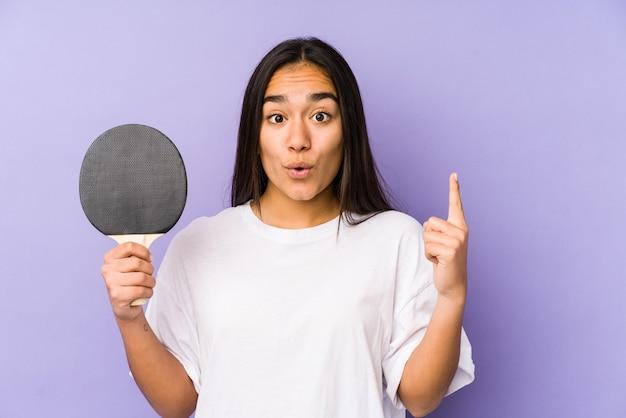 Junge indische frau, die tischtennis spielt, isoliert mit einer großen idee, konzept der kreativität.